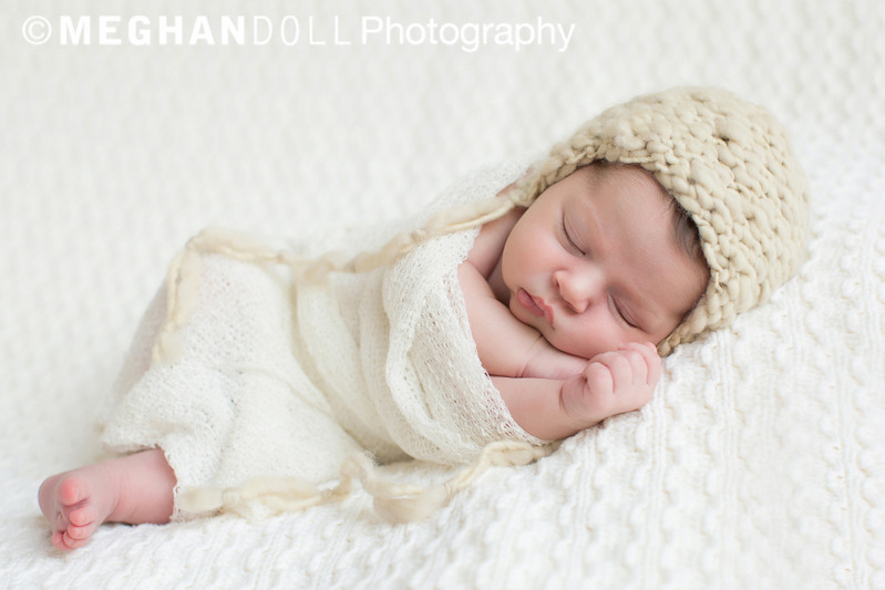 Little newborn girl sleeping soundly with adorable cream colored hat on.