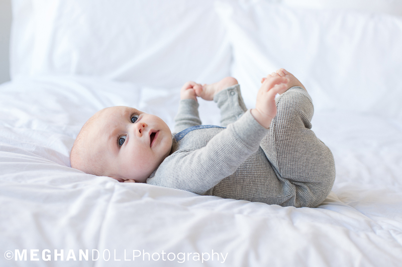3 Month Old Baby Boy in Gray Plays with his Toes on a White Bed