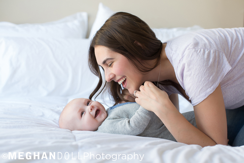 Smiling mom plays with her laughing baby boy on the big white fluffy bed