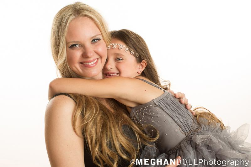 7 year old girl gives her glamorous mom a big hug