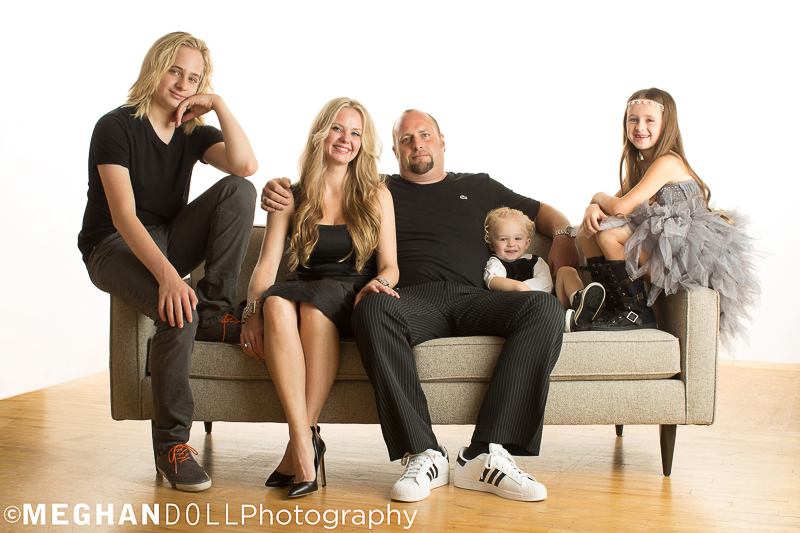 Family with three kids poses on a big couch all dressed in their best and perfectly coordinated outfits