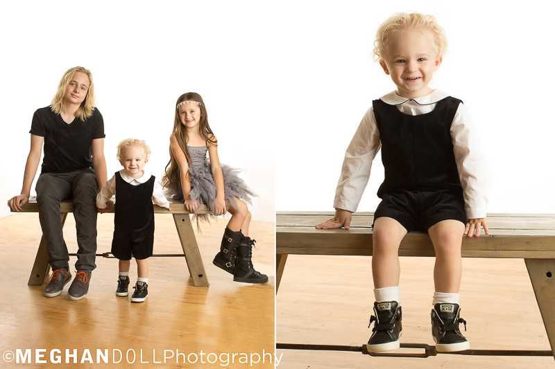 Three siblings sit nicely on a wooden bench and show off their cool style and littlest 2 year old smiles and shows off his big kid shoes