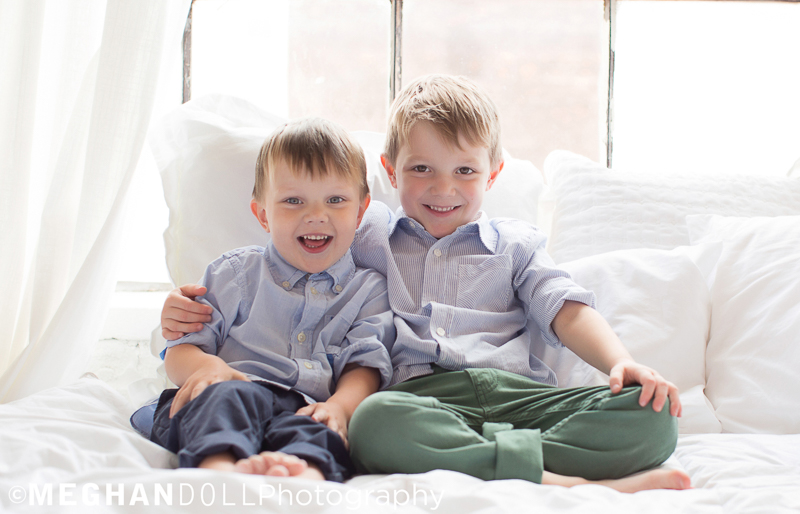 big brother wraps his arm around his little brother on the cozy bed