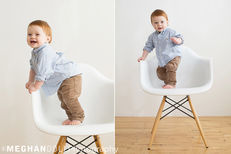 red head baby in corduroy pants stands up in big chair and laughs