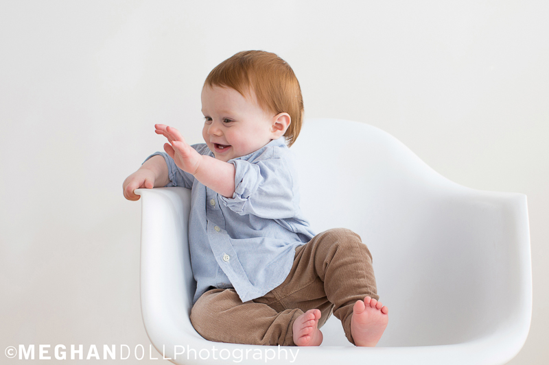 stylish baby boy drums on modern white chair and laughs