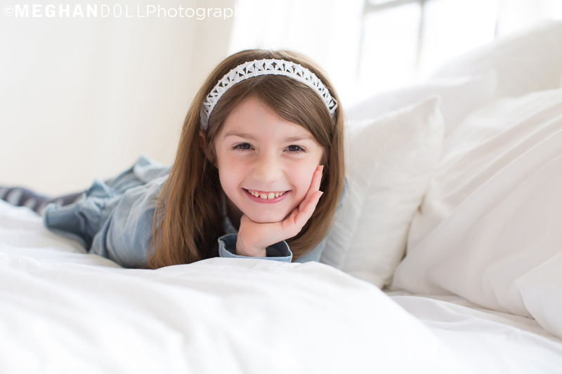little girl strikes a pose after jumping on the bed with her cousins