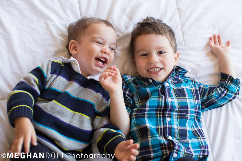 two boys in coordinating outfits lay on their backs and laugh together on a fluffy bed