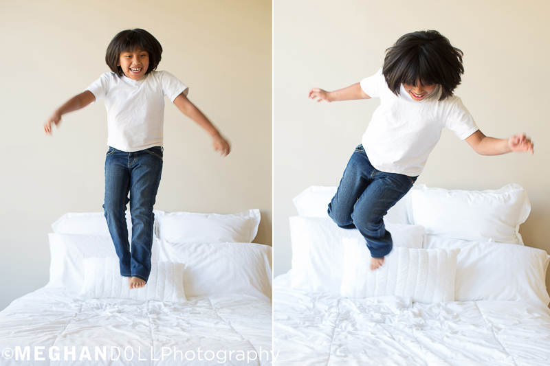 little girl in white and jeans jumps high on the bed with lots of fun energy