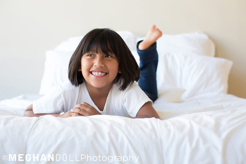 pretty little girl with short brown hair smiles into the light while laying on the fluffy white bed