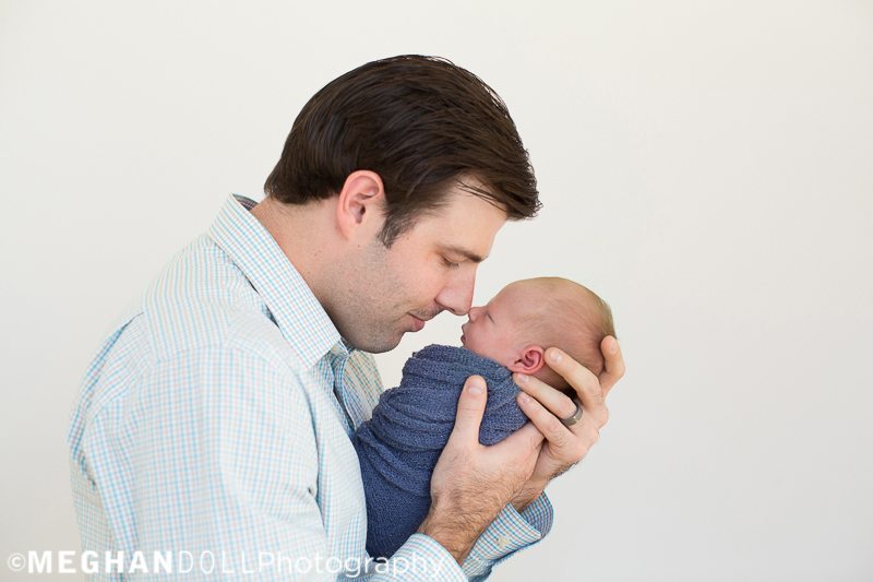dad in blue touches noses with his newborn son