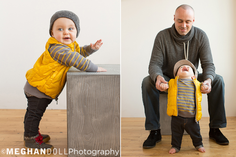 baby in yellow vest plays on big silver cube and giggles with dad