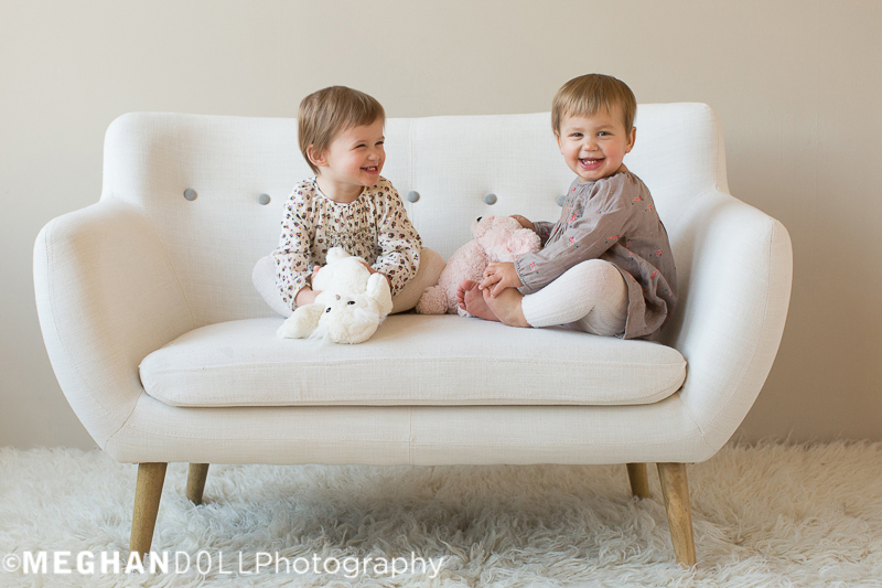 twin-two-year-old-girls-giggle-on-couch-together-holding-stuffed-animals