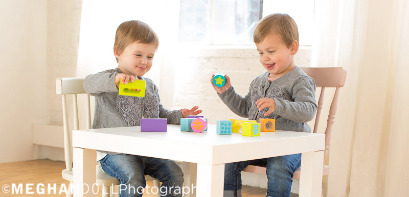 twin-two-year-old-girls-play-at-white-table-with-colorful-blocks