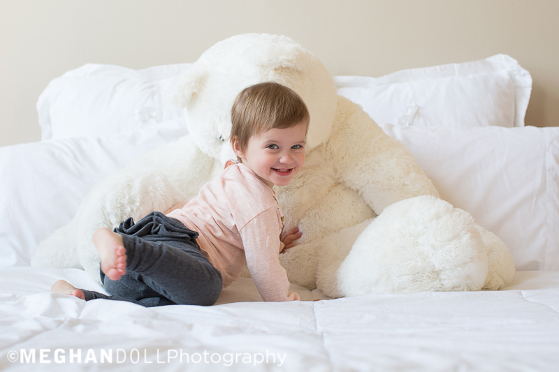two-year-old-twin-plays-on-bed-with-big-white-teddy-bear-and-smiles-while-jumping-on-it