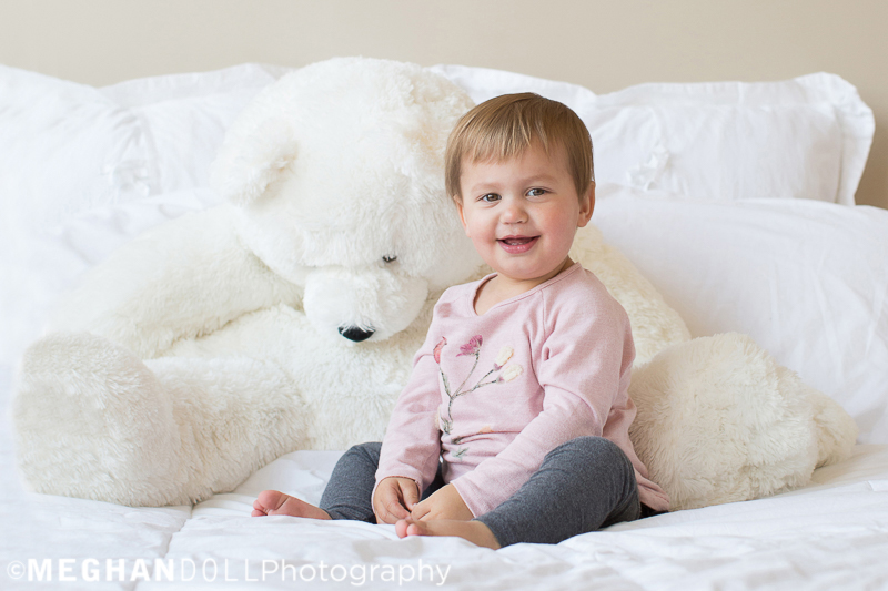 two-year-old-twin-sits-nicely-on-big-white-bed-with-big-white-bear