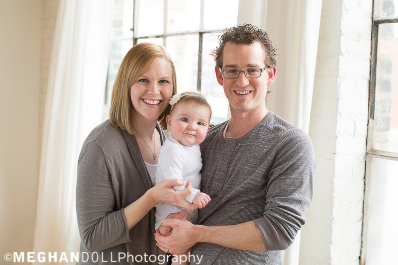 family-snuggles-their-6-month-old-daughter-by-the-windows-with-big-smiles