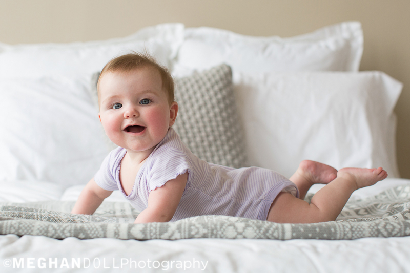 laughing-baby-greta-plays-on-her-belly-on-the-big-bed