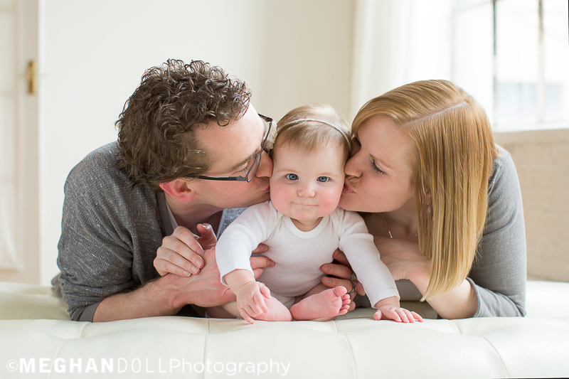 mom-and-dad-make-a-baby-sandwich-on-their-bellies-kissing-their-6-month-old-baby-girl