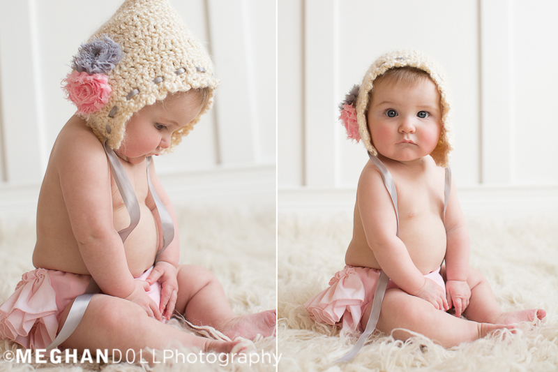precious-baby-greta-sits-on-the-white-rug-with-the-bonnet-hat-on-playing-with-her-belly