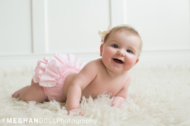 smiling-6-month-old-greta-in-pink-bloomers-on-a-fluffy-rug