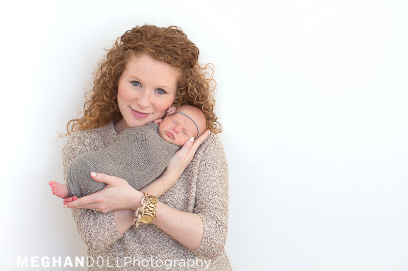 proud mom with red curly hair holds up her brand new baby girl