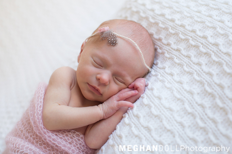 tiny newborn baby girl in pink wrap with feather headband sleeps on big white blanket