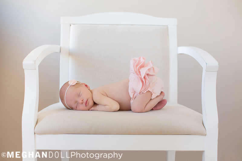 tiny newborn baby in pink ruffle bloomers sleeps peacefully on big white chair