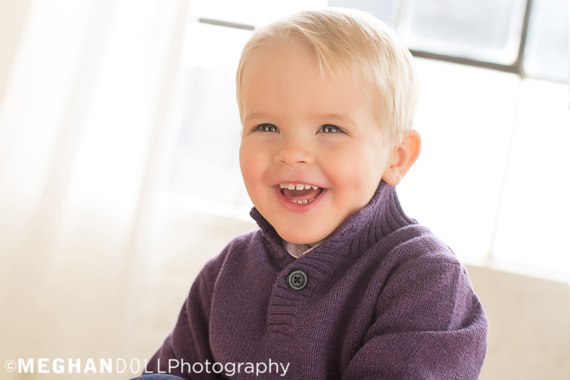 adorable two year old boy gives a big laugh while wearing a purple sweater