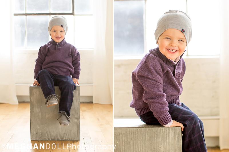two year old boy in purple and a gray beanie sits on block and laughs