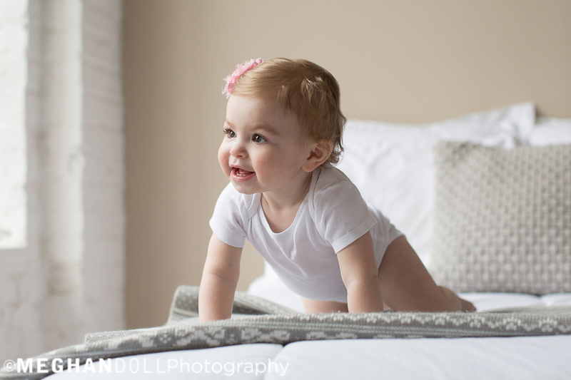 one year old baby girl with pink flower crawls on gray bed