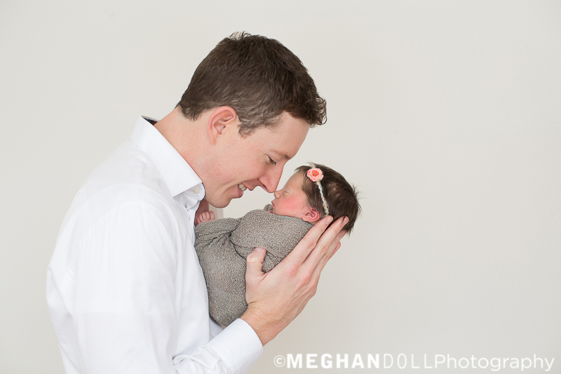 new dad touches noses with his tiny newborn baby girl in gray