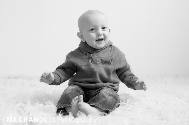 6 month old baby boy laughts on fluffy rug