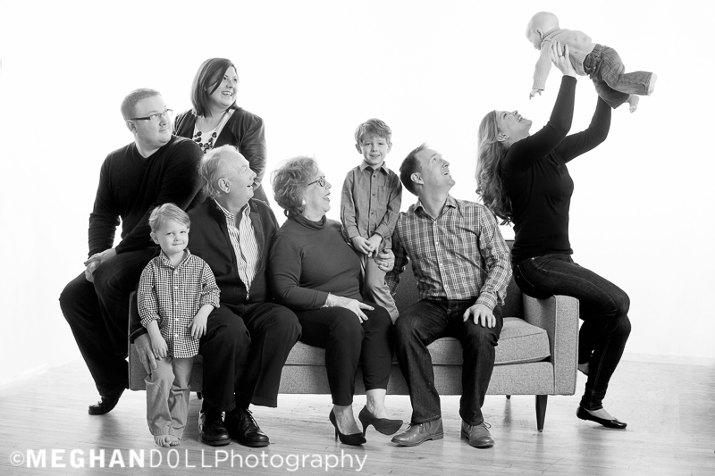 big fun family laughts together with baby in the air