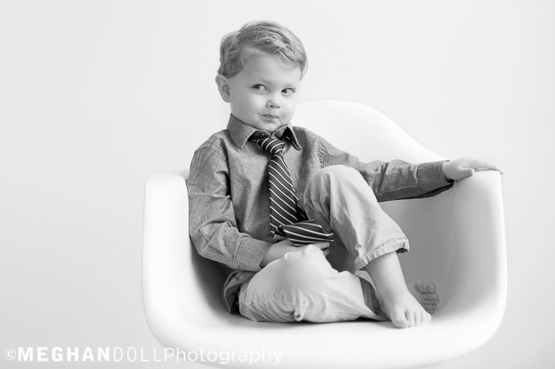 funny little boy makes a silly face while showing off his cool tie