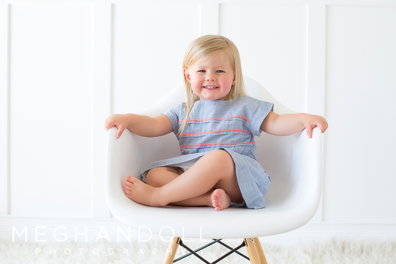 adorable-little-blonde-girl-smiles-like-a-big-girl-in-modern-chair