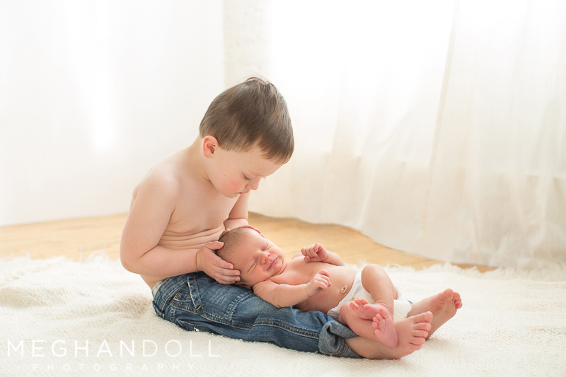 two year old big brother sits with his newborn baby brother on his lap
