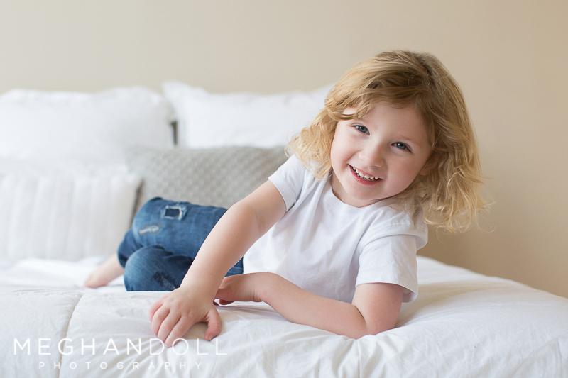 little three year old boy plays on big bed