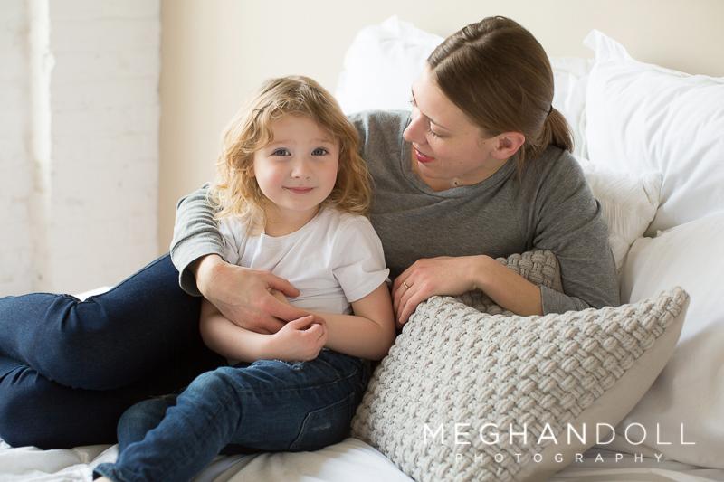 three year old boy cuddles with mom on big bed