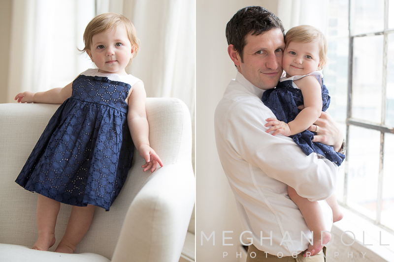 dad hugs his one year old baby girl in navy as she poses on couch