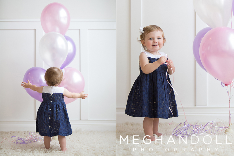 one year old baby girl plays with her pink birthday balloons