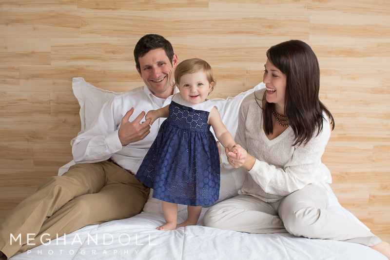 one year old baby girl plays with parents on white bed with wood wall