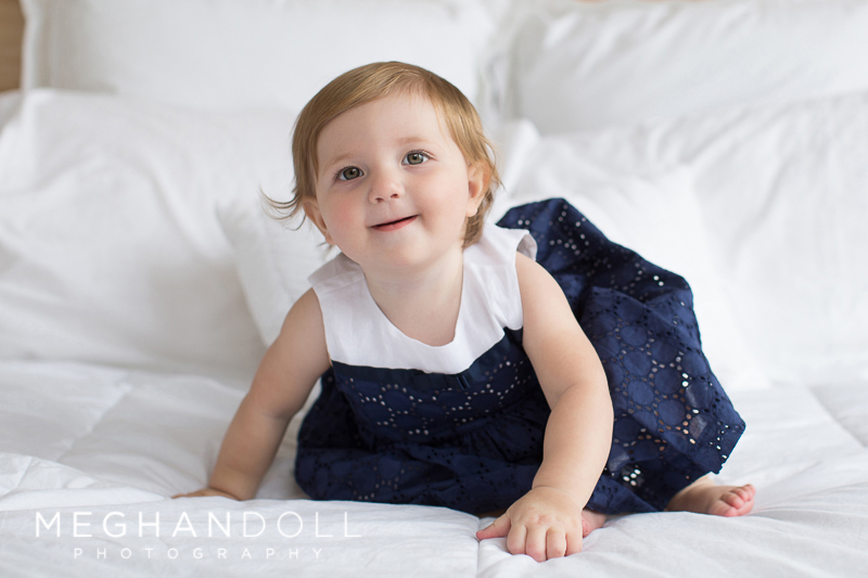 one year old girl in navy plays around on big white bed