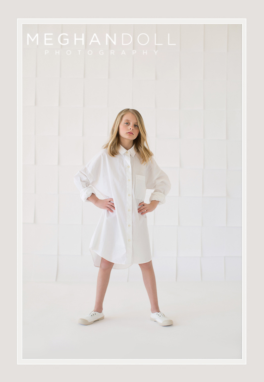 Image of strong little girl standing infront of a wall of blank sheets of paper wearing a grow ups button down shirt.