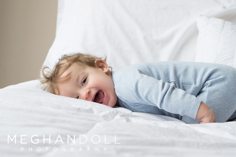 one-year-old-baby-boy-lays-on-bed-and-laughs