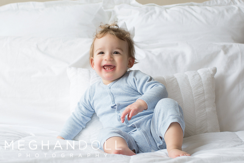 one-year-old-baby-boy-sits-and-laughs-on-bed