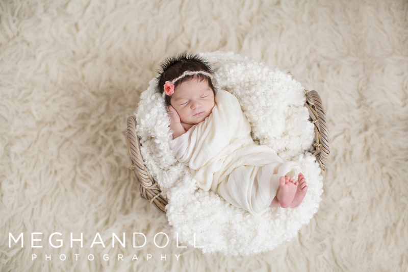 newborn-baby-girl-with-lots-of-hair-sleeps-peacefully-in-white-blanket
