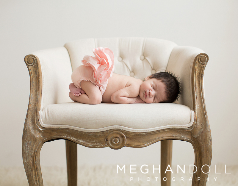 sweet-newborn-baby-girl-with-lots-of-hair-sits-in-vintage-chair