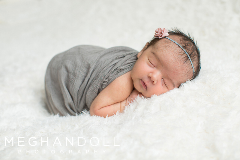 tiny-newborn-baby-girl-in-gray-with-pink-headband-curls-up-on-a-fluffy-blanket