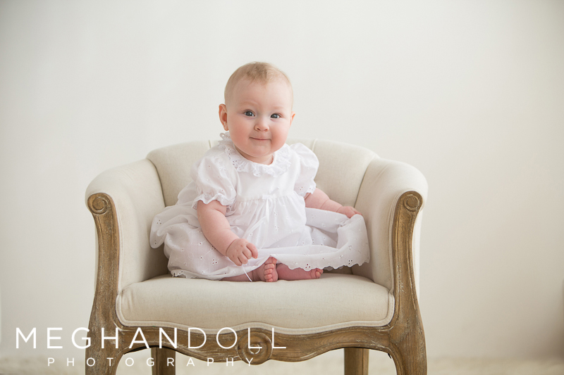 6-month-old-baby-girl-sits-like-a-big-girl-in-her-baptismal-dress
