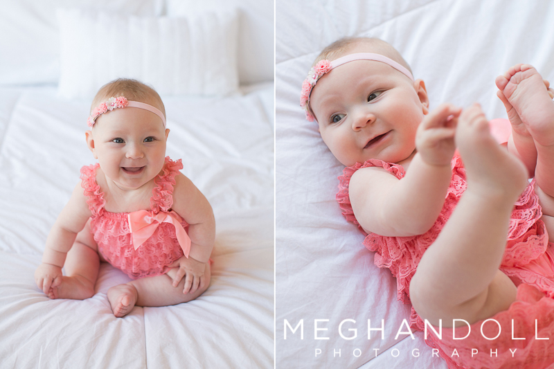 baby-girl-in-pink-romper-plays-with-her-toes-and-laughs